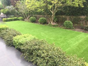 artificial lawn installed next to driveway