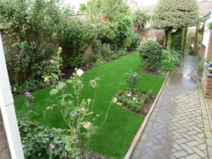 natural looking artificial grass installation around plants and borders