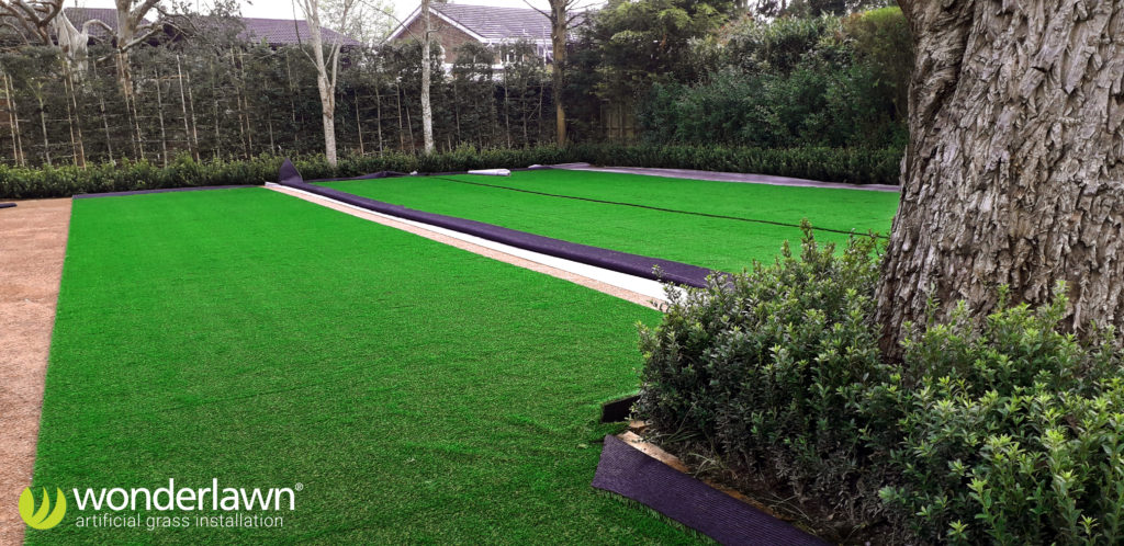 The large sections of artificial grass are rolled out and joined.