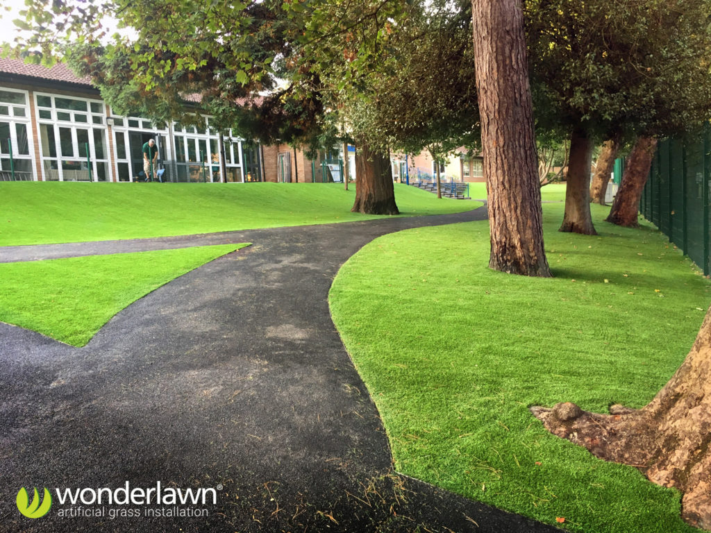 artificial grass installed in a school next to a tarmac path